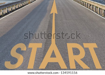 Yellow arrow and the word start on the asphalt road surface. - stock photo