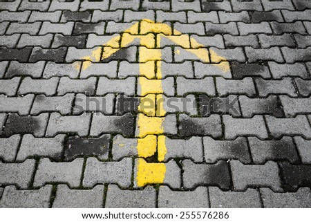 Yellow arrow painted on dark gray cobblestone pavement, road direction sign - stock photo