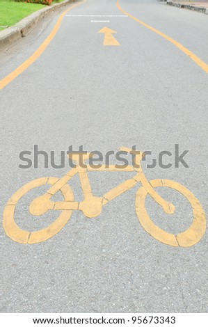 yellow arrows and bicycle sign path in the park - stock photo