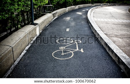 yellow arrows and bicycle sign path on the road - stock photo