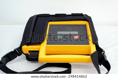 Yellow automated external mobile defibrillator and pad for rescuing patient with sudden heart shock and saving the patient from death. - stock photo