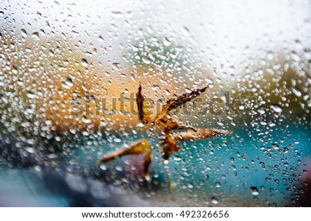 Yellow autumn leaf on the glass with drops of rain