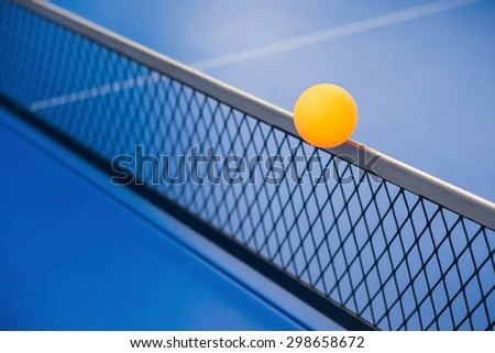yellow ball hits the racket on a blue pingpong table - stock photo