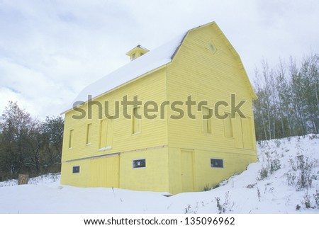 Yellow barn in a snow covered land, MI - stock photo