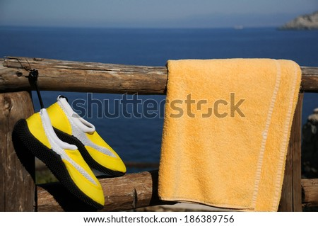 Yellow beach shoes and towel on the wooden fence against in the sea background - stock photo