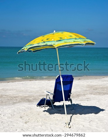 Yellow Beach Umbrella and Blue Chair on the Beach - stock photo