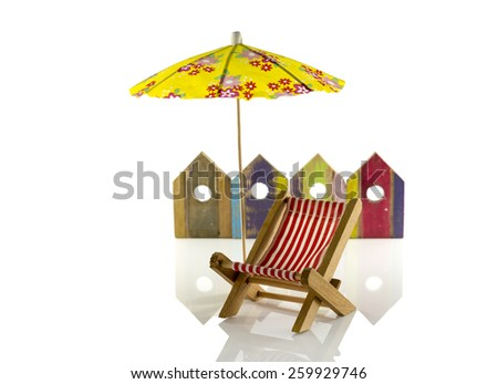 yellow beach umbrella with chair and wooden beach houses - stock photo