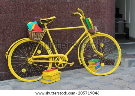 Yellow bicycle full of books near local bookstore - stock photo