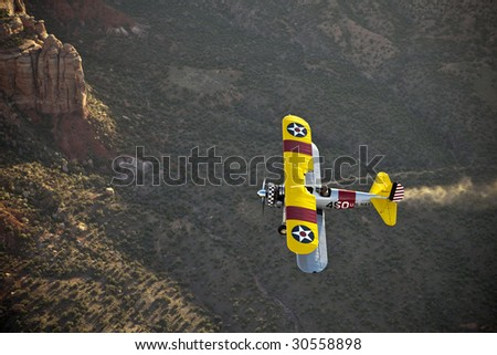 yellow biplane over rocky canyon - stock photo