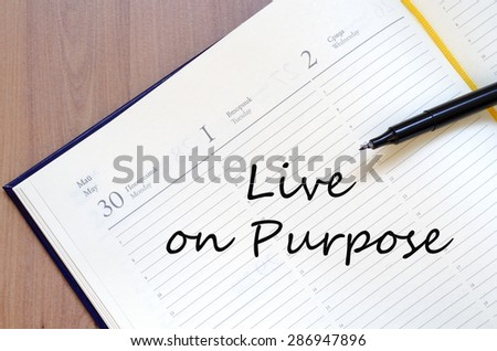 Yellow blank notepad on office wooden table Live on purpose concept