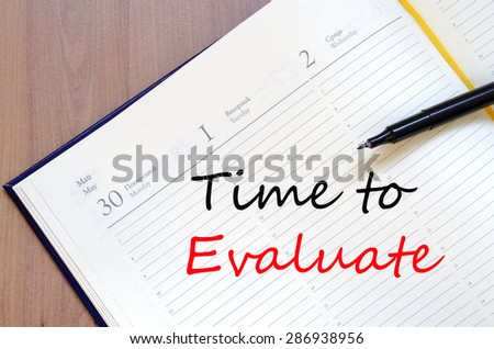 Yellow blank notepad on office wooden table Time to evaluate concept