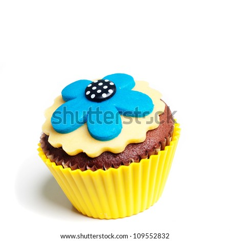 Yellow blue flower decorated cupcake isolated