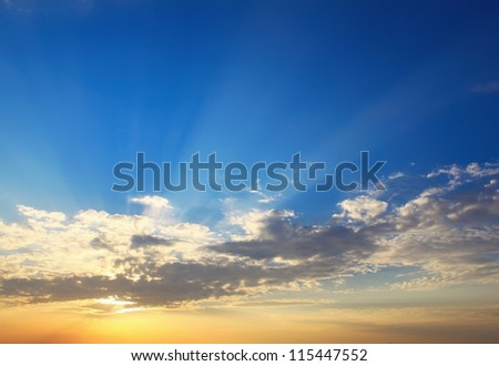 Yellow blue sunset sky with sunlight - stock photo
