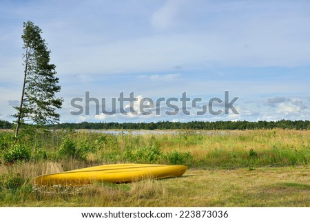 Yellow boat on shore of marshy lake, Finland - stock photo