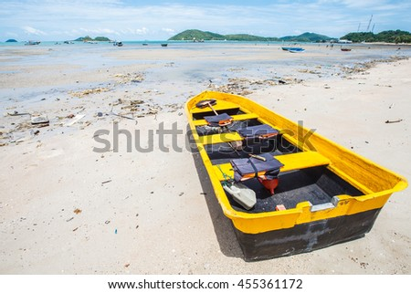 Yellow boat on the beach dirty. - stock photo