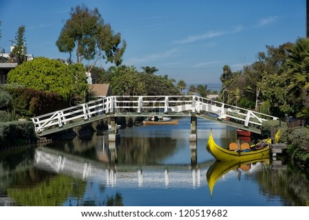 yellow boat on the venice canals in los angeles - stock photo