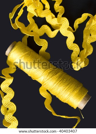 yellow bobbin and yellow lace on black - stock photo