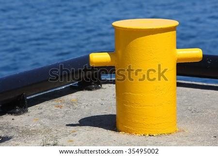 Yellow bollard at a marina. - stock photo