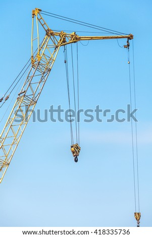 Yellow boom crane with two hooks on the background of blue sky  - stock photo