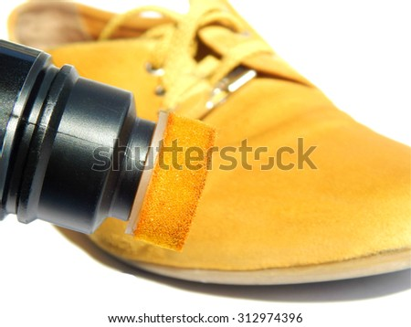 Yellow boot and yellow paint for shoes on white background - stock photo