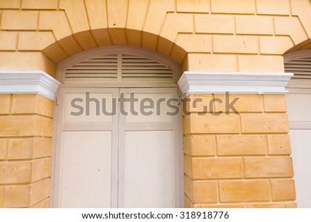 yellow brick building with white windows - stock photo
