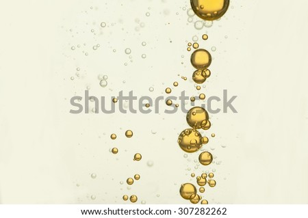 Yellow bubbles flowing over a white background - stock photo