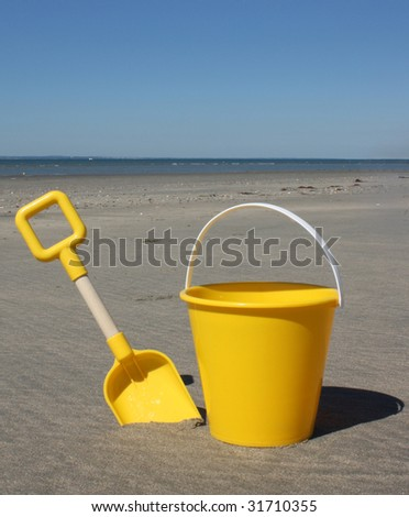 Yellow bucket and spade - stock photo
