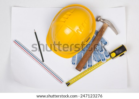 yellow builder's helmet and work tools over white background - stock photo