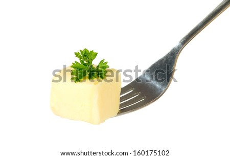 Yellow butter with parsley is being hold with fork, food concept - stock photo