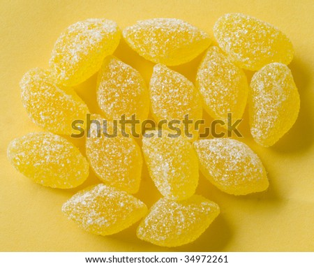 yellow candies with white sugar on yellow background with yellow shadows - stock photo