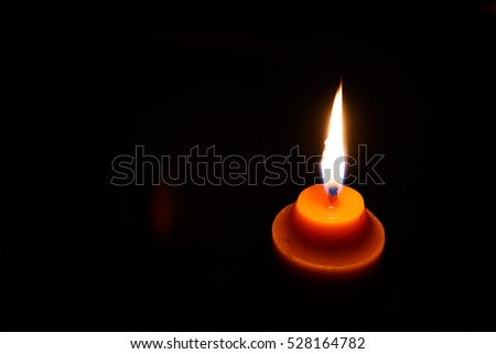 yellow candle isolation on black background photo