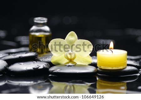Yellow candle with bottle of essential oil and orchid on pebble - stock photo