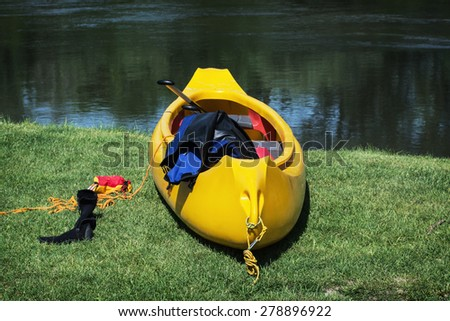 Yellow canoe boat on the shore. Water sports. - stock photo