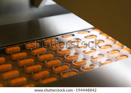 Yellow capsules packed in tablet packing machine - stock photo