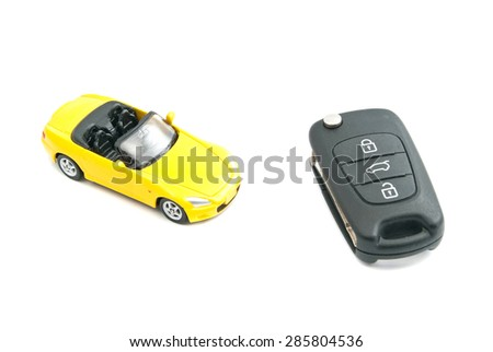 yellow car and black car keys on white - stock photo