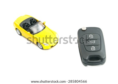 yellow car and black car keys on white background - stock photo