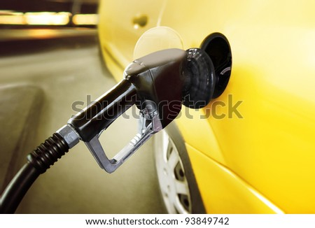 yellow car at gas station being filled with fuel - stock photo