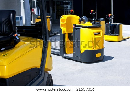 Yellow cargo pallet transporters and fork lifters - stock photo
