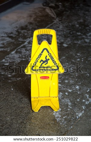 yellow caution sign - warning sign at an entrance to the icy way - stock photo