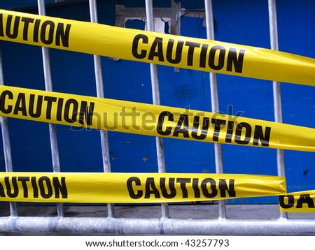 Yellow caution tape on a metal barrier - stock photo