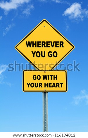 Yellow cautionary road sign Wherever You Go, Go With Your Heart against a blue sky - stock photo