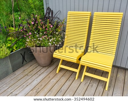 Yellow chairs and big pot with flowers decorating house exterior.