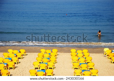 Yellow chairs on the beach - stock photo