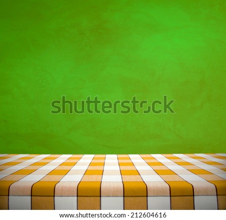 Yellow checkered tablecloth on green wall background - stock photo