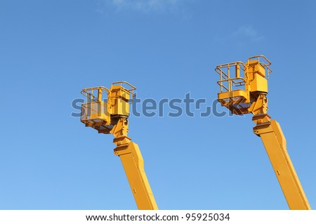 Yellow cherry picker against a blue sky - stock photo