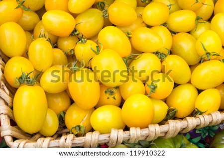 Yellow cherry tomatoes on display in wicker basket at the market - stock photo