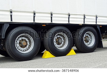 Yellow chocks at the wheel of a truck-trailer