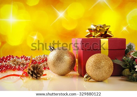 Yellow Christmas decoration on a white table methacrylate. With red gift box with gold ribbon, two golden balls and pearls. Front view. Horizontal composition.