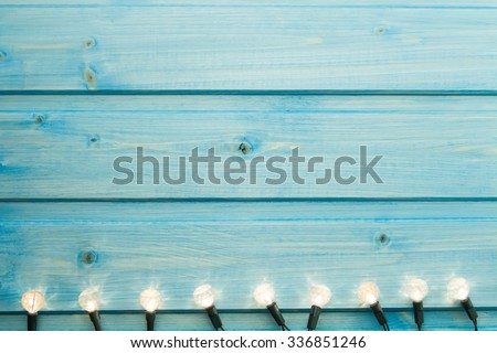yellow Christmas lights on a blue wooden background. - stock photo