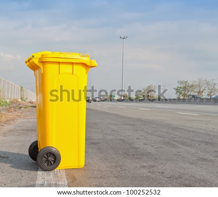 Yellow clean garbage bin on highway - stock photo